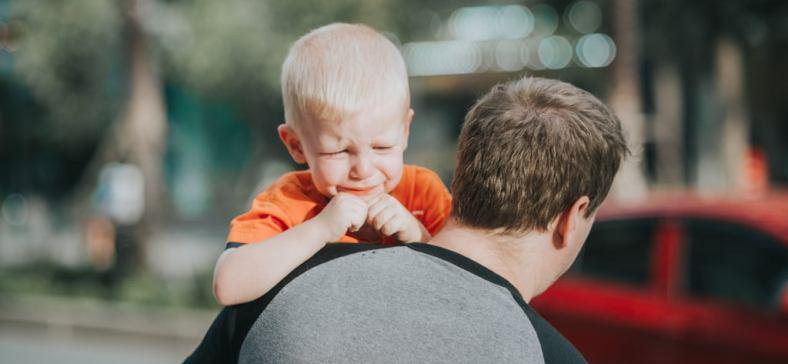 Gambar: Anak menangis yang digendong orang tuanya.