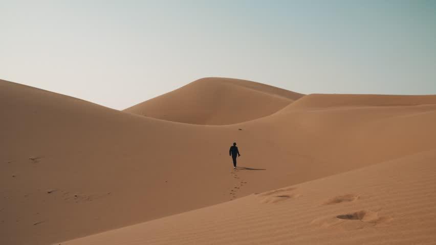 Seseorang berjalan sendiri di padang pasir.